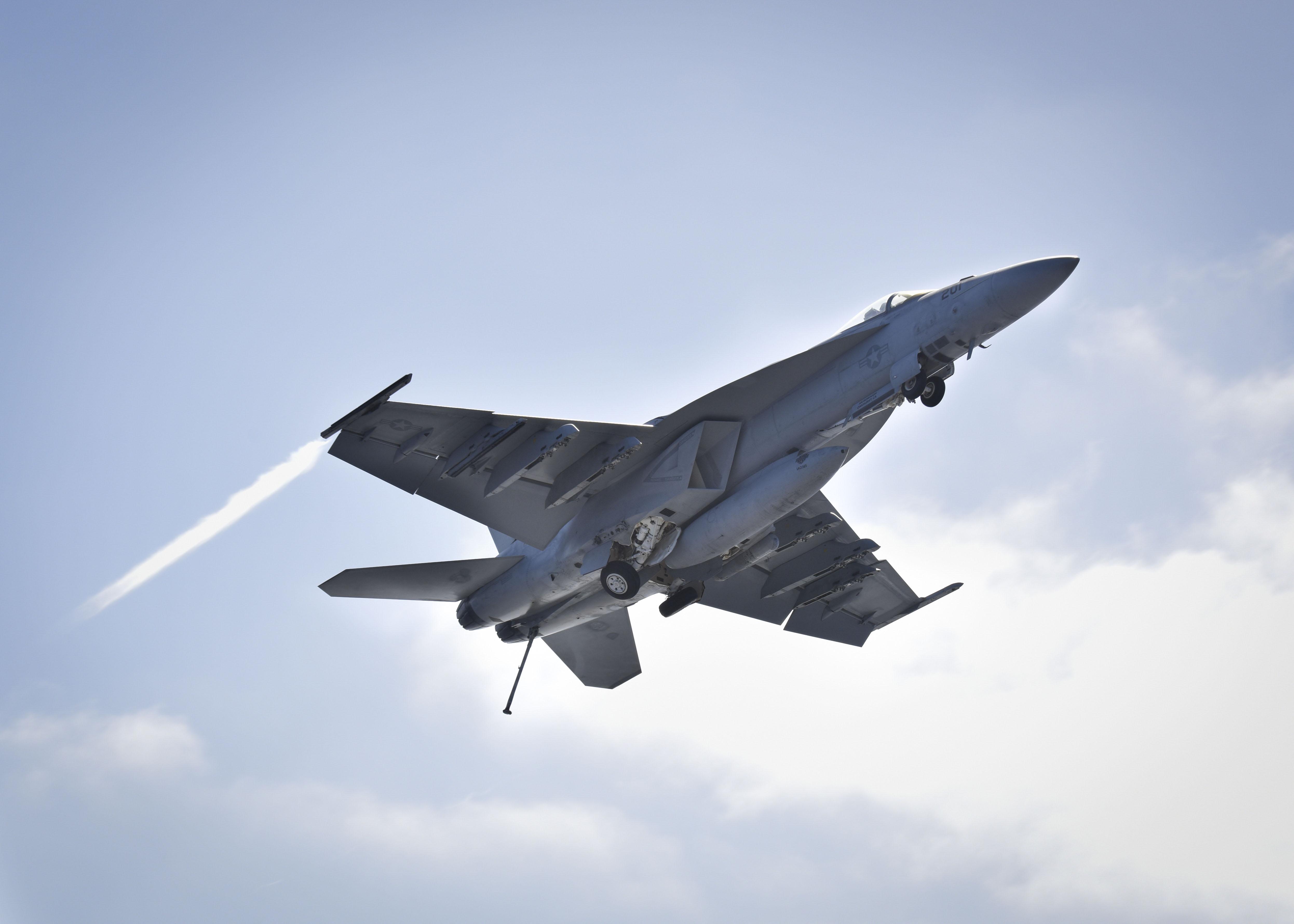 F/A – 18E flys over USSNimitz