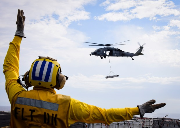 PACIFIC OCEAN (Oct. 24, 2016) - A Sailor assigned to USS Nimitz (CVN 68) directs an MH-60S Sea Hawk from the Eightballers of Helicopter Sea Combat Squadron (HSC) 8 during an at-sea ammunition onload with the dry cargo/ammunition ship USNS Wally Schirra (T-AKE 8). Nimitz is underway conducting an ordnance-handling evolution in preparation for an upcoming 2017 deployment. (U.S. Navy photo by Seaman Weston A. Mohr/Released)